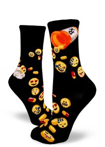 Pills with emoji faces pour out of prescription bottles on black women's crew socks.