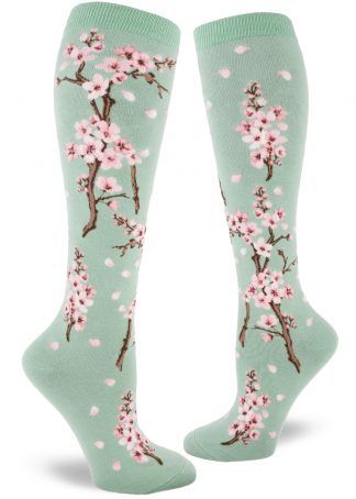 Cherry blossom knee socks with a pink floral design on a light green background.